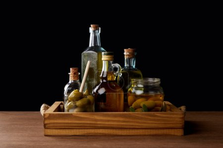 various bottles of aromatic olive oil and jar with green olives on wooden table on black background