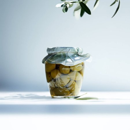 jar of aromatic oil with green olives and branch on white background