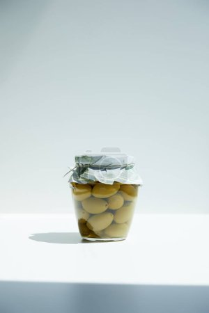 jar of aromatic oil with green olives on white table
