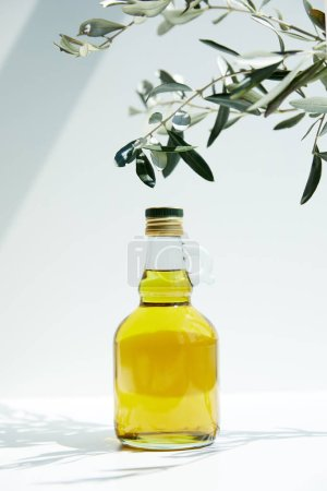 closeup view of bottle of aromatic olive oil and branches on white table
