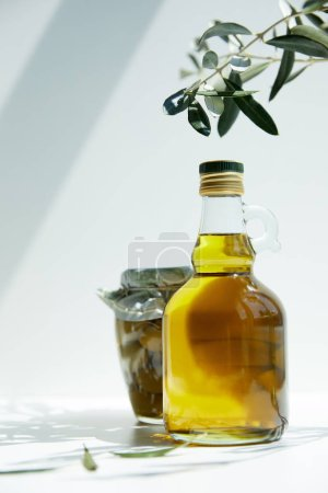 bottle of aromatic olive oil, branch and jar with green olives on table