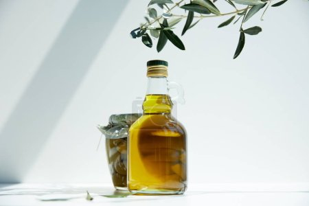 bottle of aromatic olive oil, branches and jar with green olives on white table