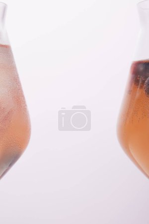 partial view of two glasses with lemonade isolated on grey background