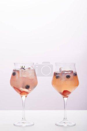 deux verres de limonade avec des glaçons, romarin, fraises et bleuets isolés sur fond gris