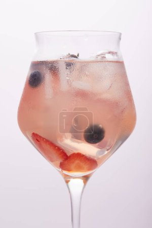 close up shot of glass of lemonade with ice cubes, strawberries and blueberries isolated on grey background
