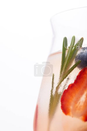 partial view of glass of lemonade with rosemary, blueberry and strawberry isolated on white background