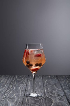 glass of lemonade with ice cubes, blueberries and strawberries on grey background