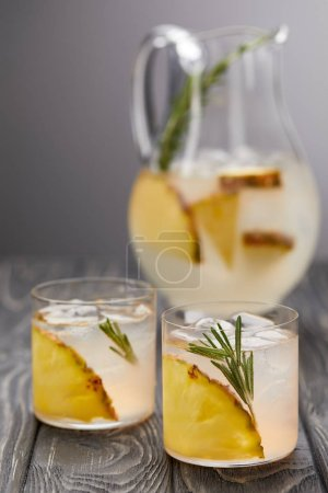 jug of lemonade with pineapple and rosemary, two glasses of lemonade with pineapple pieces, ice cubes and rosemary on grey wooden tabletop