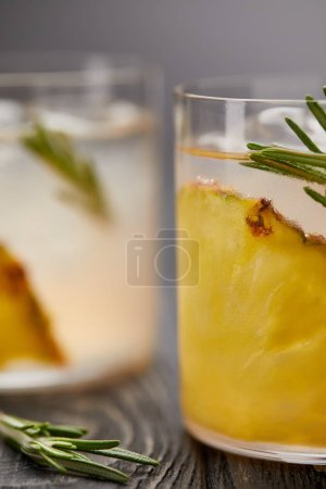 close up shot of two glasses of lemonade with pineapple pieces, ice cubes and rosemary on grey wooden tabletop