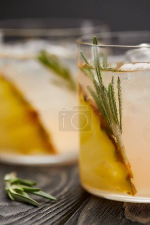 Photo for Close up image of two glasses of lemonade with pineapple pieces, ice cubes and rosemary on grey wooden tabletop - Royalty Free Image