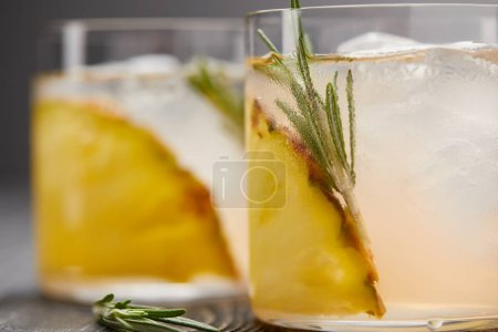 Photo for Selective focus of two glasses of lemonade with pineapple pieces, ice cubes and rosemary on grey wooden tabletop - Royalty Free Image