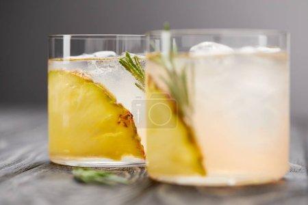 Photo pour Deux verres de limonade avec des morceaux d'ananas, de glaçons et de romarin sur une table en bois grise - image libre de droit