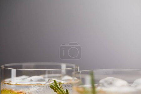 Photo for Partial view of two glasses of lemonade with pineapple pieces, ice cubes and rosemary on grey background - Royalty Free Image