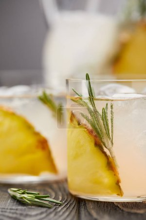 jug with lemonade and two glasses of lemonade with pineapple pieces, ice cubes and rosemary on grey wooden tabletop