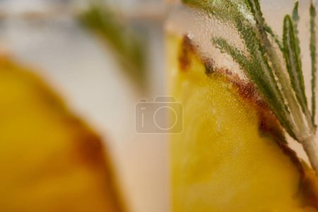 selective focus of two glasses of lemonade with pineapple pieces, ice cubes and rosemary