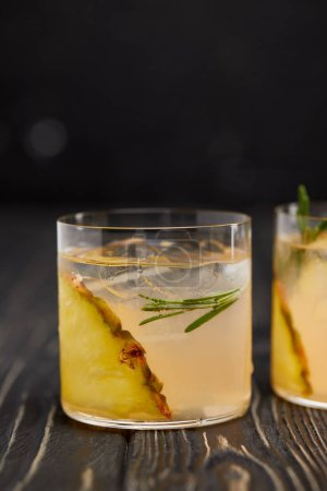 Photo for Partial view of two glasses of lemonade with pineapple pieces, ice cubes and rosemary on grey wooden tabletop - Royalty Free Image