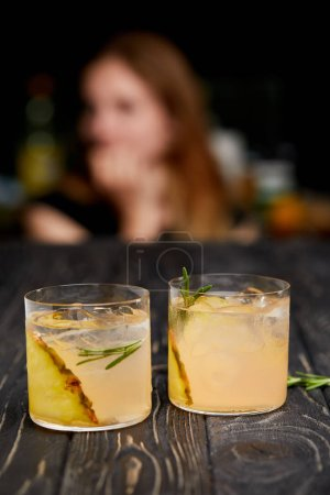 selective focus of pineapple pieces, ice cubes, rosemary in two glasses of lemonade and woman on blurred background