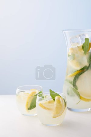 Photo for Jug and two glasses of lemonade with mint leaves, ice cubes and lemon slices on blue background - Royalty Free Image