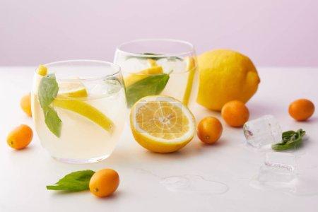 Photo pour Deux verres de limonade avec des feuilles de menthe, des glaçons et des tranches de citron entourés de kumquats et de citrons sur fond violet - image libre de droit