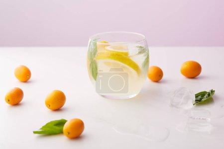 Photo pour Verre de limonade avec des feuilles de menthe et de tranches de citron entourées de glaçons, kumquats sur fond violet - image libre de droit