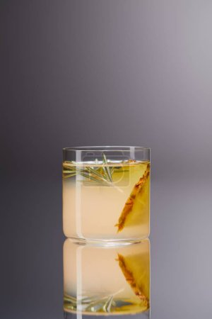 glass of fresh pineapple cocktail on reflective surface and on grey