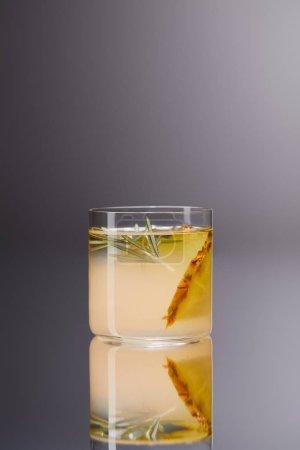 vaso de cóctel de piña fresca en superficie reflectante y en gris