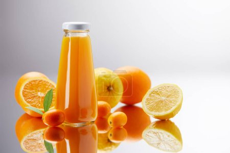 bottle of fresh juice with oranges, lemons and kumquats on reflective surface