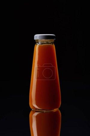 bottle of fresh orange juice on reflective surface isolated on black