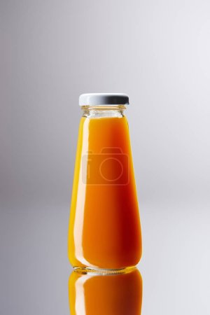 bottle of fresh orange juice on reflective surface