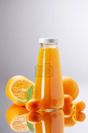 bottle of fresh orange juice with oranges and kumquats on reflective surface