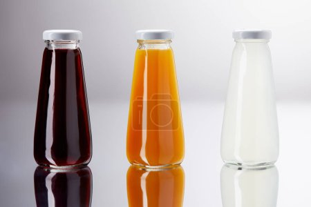 row of bottles of various juice on reflective surface