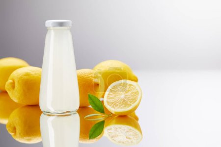 glass bottle of fresh lemonade with lemons on reflective surface and on grey