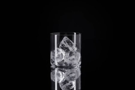 single glass with ice cubes on reflective surface isolated on black