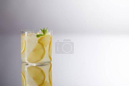single glass of fresh lemonade on reflective surface and on grey