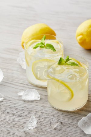 Photo for Glasses of delicious lemonade with ice and lemons on wooden surface - Royalty Free Image