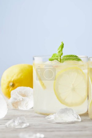 fresh glasses of lemonade with ice and lemon on wooden surface