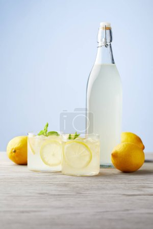 bottle and glasses of fresh italian limoncello on wooden tabletop