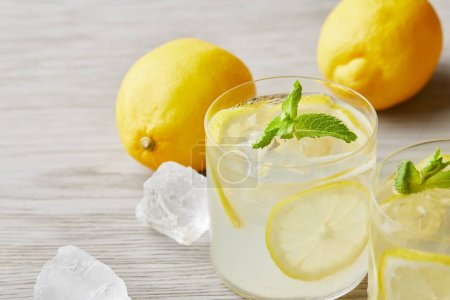 Photo for Cooled lemonade glasses with ripe lemons on wooden surface - Royalty Free Image