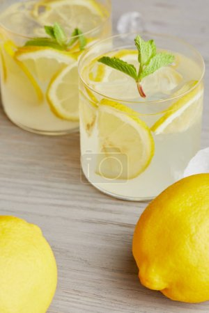Photo for Close-up shot of glasses of lemonade with ripe lemons on wooden surface - Royalty Free Image