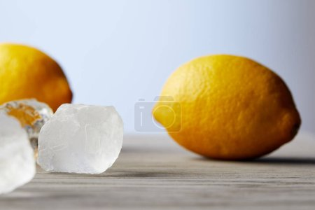 close-up shot of lemons and ice cubes on wooden surface