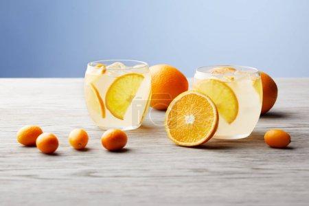 Photo pour Verres de délicieuse limonade aux oranges mûres sur plateau en bois - image libre de droit