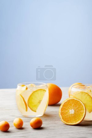 glasses of cooled delicious lemonade with ripe oranges on wooden tabletop