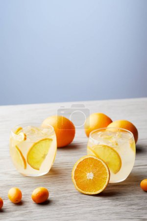 glasses of fresh lemonade with ripe oranges on wooden tabletop