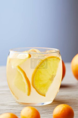 close-up shot of glass of fresh lemonade with ripe oranges on wooden surface