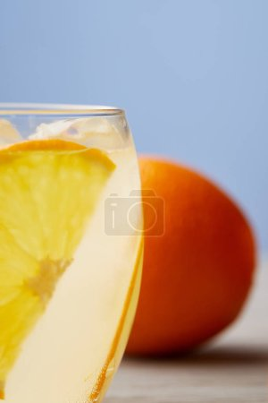 close-up shot of glass of lemonade with ripe orange on wooden surface