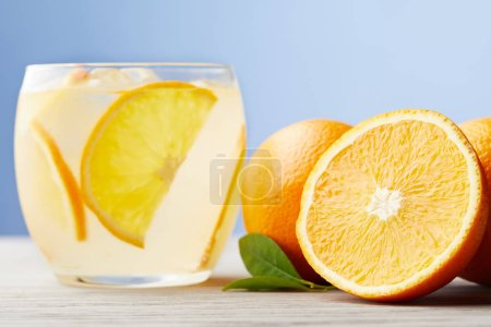 glass of fresh lemonade with ripe oranges on wooden table