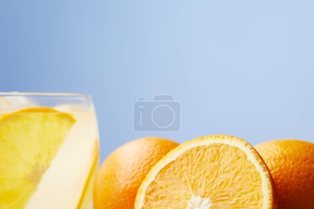 glass of refreshing lemonade with oranges on wooden table
