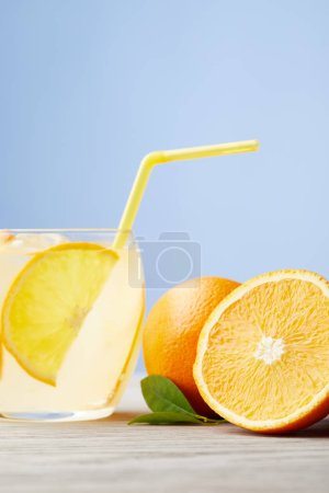 glass of delicious lemonade with oranges on wooden table
