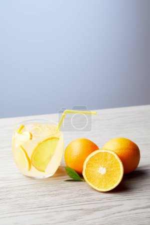 glass of fresh lemonade with oranges on wooden table