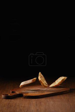 Slices of wholegrain bread falling on wooden table surface